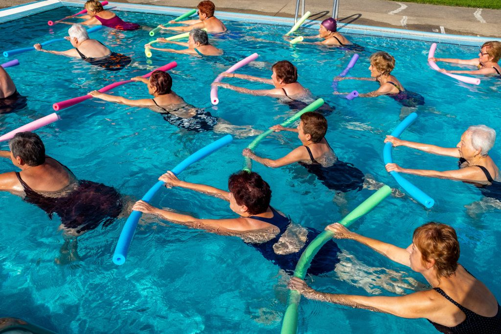 Group of senior women working out with foam noodles. Side view of active ladies in outdoor swimming pool.